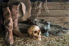 Menselijke schedel en cowboylaarzen op schuurachtergrond Stock Afbeeldingen