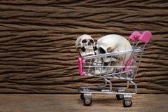 Menselijke schedel in het winkelen auto op oude mooie houten achtergrond royalty-vrije stock afbeeldingen