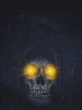 Menselijke schedel in kap met het branden van ogen op donkere achtergrond hallow Stock Fotografie