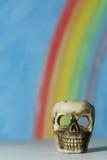 Menselijke schedel met een blauwe hemel en regenboogachtergrond Royalty-vrije Stock Afbeeldingen