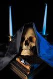 Menselijke schedel op een boek naast de klok Concept Royalty-vrije Stock Foto's