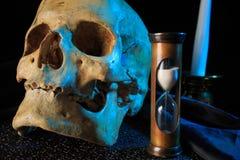 Menselijke schedel op een boek naast de klok Concept Stock Fotografie