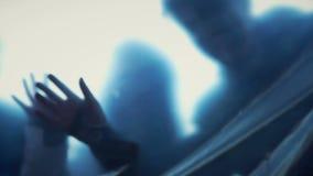 Menselijke silhouetten achter transparante film het uitrekken zich handen, enge nachtmerrie stock footage