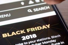 Menselijke vingerduim over de tekst van Black Friday 2018 bij het winkelen app op de close-up van het smartphonescherm stock afbeeldingen