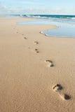 Menselijke voetafdrukken op het strandzand stock foto's