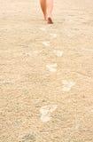 Menselijke voetafdrukken op het strandzand dat weg leidt Royalty-vrije Stock Afbeeldingen
