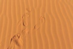 Menselijke voetafdrukken op woestijn golvend zand Royalty-vrije Stock Foto's