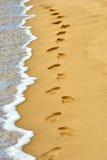 Menselijke voetafdrukken op zand bij het strand Royalty-vrije Stock Afbeelding