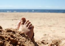 Menselijke voeten in het zand door het overzees Royalty-vrije Stock Afbeeldingen