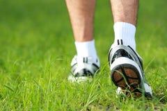 Menselijke voeten in loopschoenen aan stap op het gras Stock Afbeelding