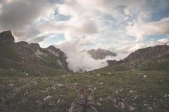 Menselijke voeten met wandelingslaarzen die op gras bij de bovenkant van alpiene vallei met toneelwolken liggen die bij zonsonder Stock Afbeeldingen