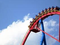 Mensen in achtbaan againt heldere blauwe hemel Royalty-vrije Stock Foto