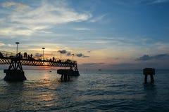 Mensen bij de visserij van pijler bij zonsondergang Stock Fotografie