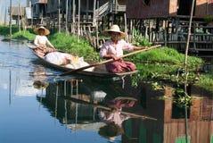 Mensen bij het roeien van een boot bij het dorp van Maing Thauk Stock Fotografie