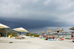 Mensen bij het strand en de donkere wolken Royalty-vrije Stock Foto