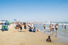 Mensen bij het strand in zonnige dag Stock Afbeeldingen