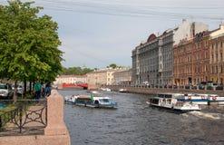 Mensen in boten dichtbij Rode Brug St Petersburg Rusland Stock Afbeeldingen