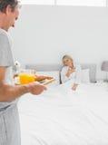 Mensen brengend ontbijt in bed aan zijn verraste partner Royalty-vrije Stock Fotografie