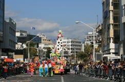 Mensen in Carnaval-kostuums en een vlotter die zich langs een straat bewegen stock foto