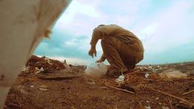 Mensen dakloze stortplaats in stortplaatsdaklozen die voedsel onder het huisvuil zoeken de sociale mens van de de armoedehonger v stock video