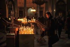 Mensen in de kerk en de lichte kaarsen royalty-vrije stock fotografie