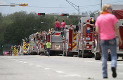 Mensen in de straat met brandmotoren en een vrouw die in een parade in kleine stad Amerika lopen Royalty-vrije Stock Fotografie