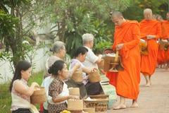 Mensen die aalmoes geven aan boeddhistische monniken op de straat, Luang Prabang, 20 JUNI 2014 Stock Afbeelding