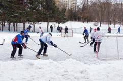 Mensen die amateurhockey in de stadsijs het schaatsen piste spelen De winter het spelen, pret, sneeuw royalty-vrije stock foto's