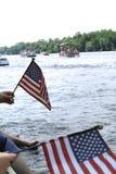 Mensen die Amerikaanse vlaggen golven bij het overgaan van pontonparade aangezien zij op rand van dok zitten Royalty-vrije Stock Foto's