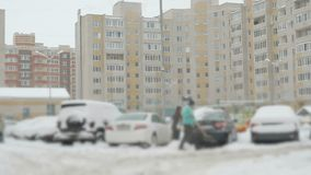 Mensen die auto van sneeuw schoonmaken stock footage