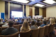 Mensen die Bedrijfsconferentiezitting voor de Gastheer bijwonen stock fotografie