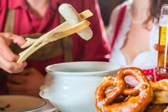 Mensen die in Beierse Tracht in restaurant of bar eten Royalty-vrije Stock Afbeeldingen