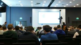 Mensen die bij conferentieauditorium zitten met het scherm en wachten voor stock videobeelden