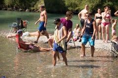 Mensen die bij de rivier koelen Stock Afbeeldingen