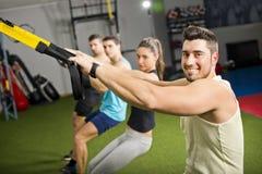 Mensen die bij gymnastiek trx oefeningen doen Stock Foto's