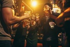 Mensen die bij nachtclub met cocktails genieten van Stock Foto