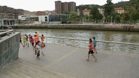 Mensen die bij rivieroever, gezonde levensstijlpromotiecampagne in grote stad lopen stock footage