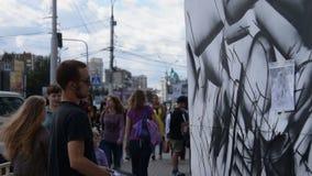 Mensen die bij werkende graffitikunstenaars letten op stock video