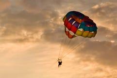Mensen die bij zonsondergang in mooi licht parasailing royalty-vrije stock fotografie