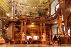 Mensen die binnen de Oostenrijkse Nationale Bibliotheek met oud luxemeubilair ontspannen Stock Afbeelding