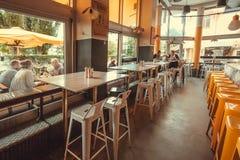 Mensen die binnen en buiten moderne koffie met bar en lege lijsten dineren Stock Fotografie