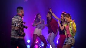Mensen die blij en bij een nachtclub het gloeien stroboscooplichten dansen Rook achtergrond stock video