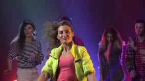 Mensen die blij en bij een nachtclub het gloeien stroboscooplichten dansen Rook achtergrond stock footage
