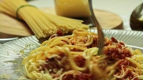 Mensen die Bolognese spaghettideegwaren en kaas eten stock footage