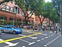 Mensen die Boomgaardweg, Singapore kruisen Stock Afbeeldingen