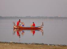 Mensen die boot op meer roeien bij zonsopgang in Mandalay, Myanmar Stock Foto's