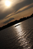 Mensen die boot roeien bij zonsondergang Royalty-vrije Stock Foto's