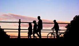 Mensen die brug in zonsondergang kruisen Royalty-vrije Stock Foto