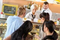 Mensen die cakes kopen bij de desserts van de cafetariarij Stock Afbeeldingen
