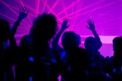 Mensen die in club met laser dansen Stock Foto